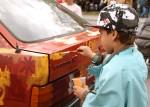 Teatterikone puffasi Koiratorpan keisari –näytelmäänsä antamalla lapsille mahdollisuuden maalata autoa Seminaarinkadulla vuonna 2011. Kuva: Mikko Åman